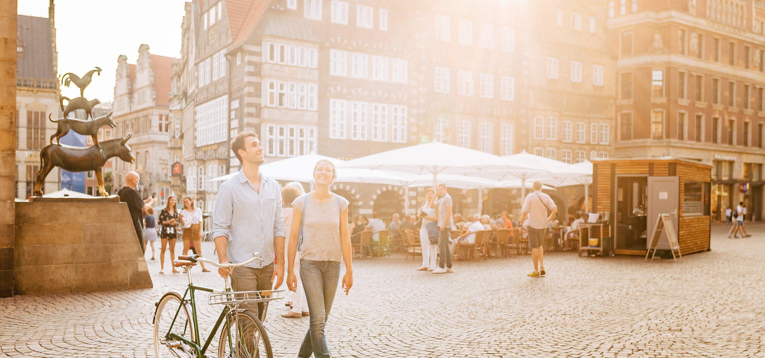 Zwei Personen stehen auf dem Bremer Marktplatz bei Sonnenschein.