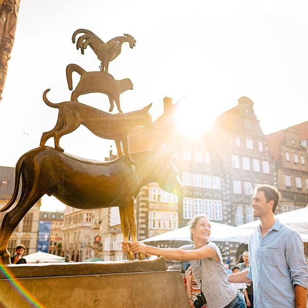 Zwei Personen stehen vor den Bremer Stadtmusikanten. Eine von ihnen berührt die Beine des Esels.
