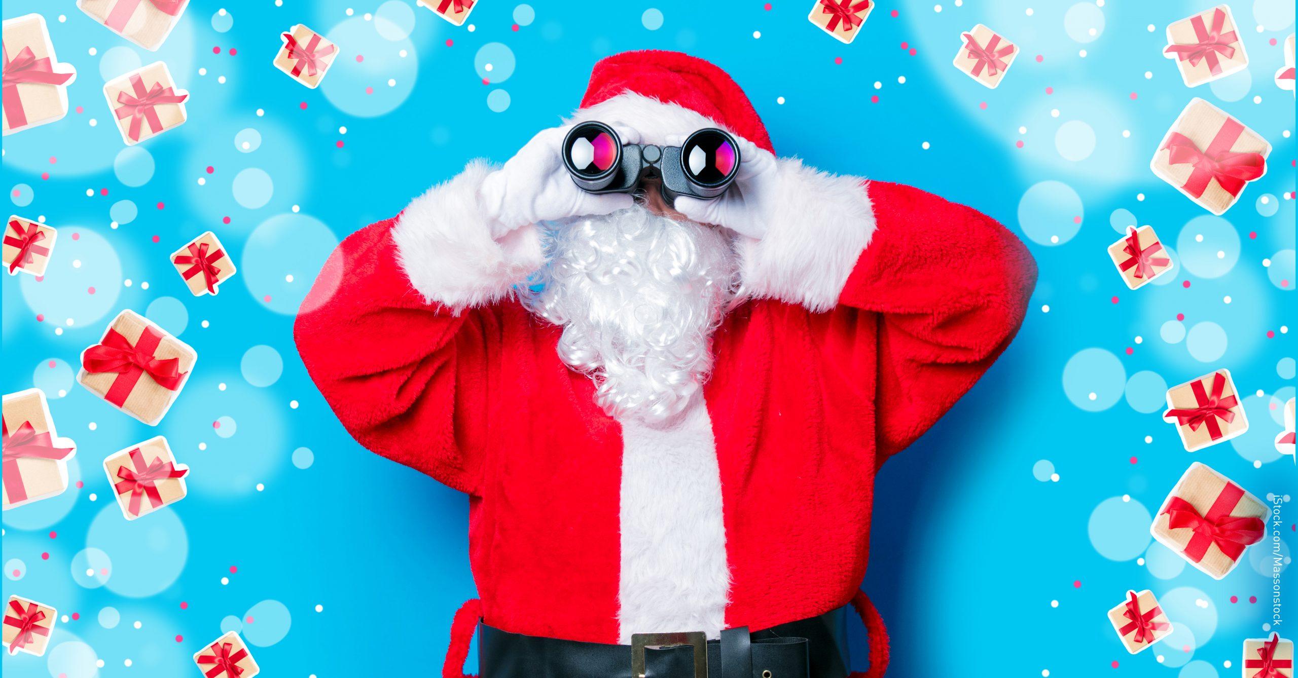 Ein Weihnachtsmann blickt durch ein Fernglas.
