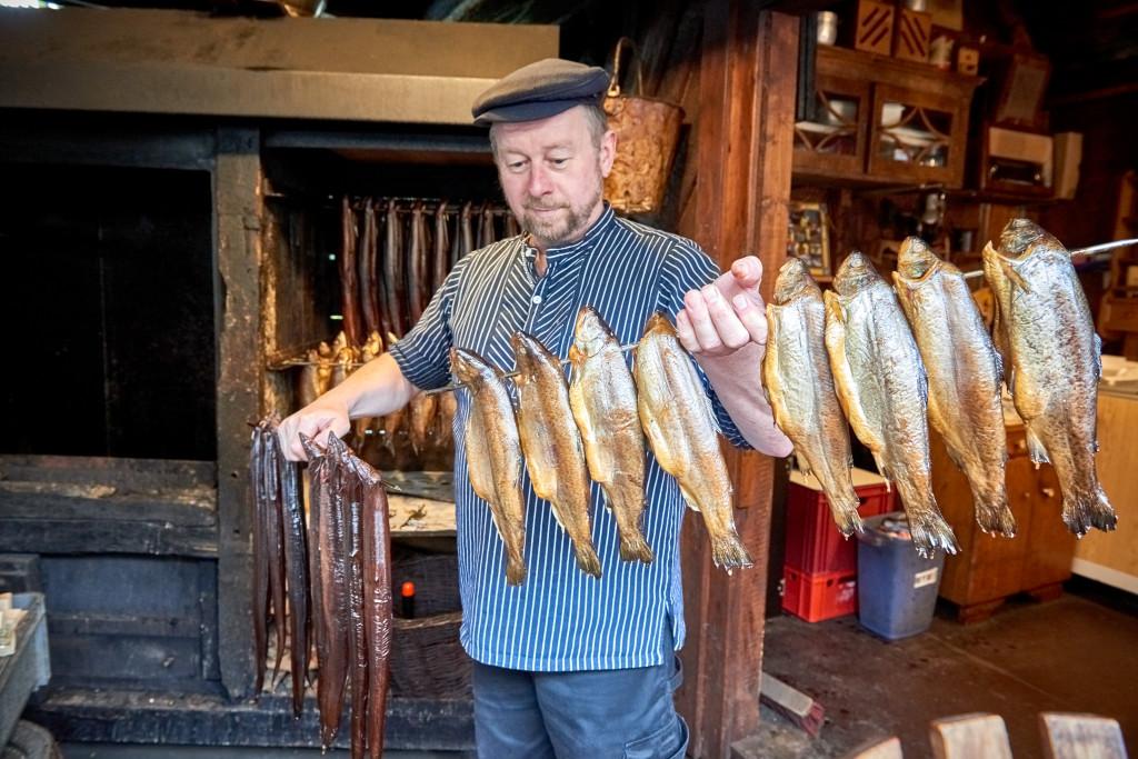 Ein Mann steht vor einigen Forellen am Seil.