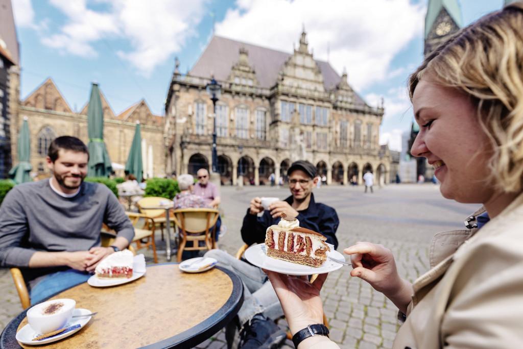 Drei Personen sitzen an einem Tisch beim Kuchenessen auf dem Bremer Marktplatz.