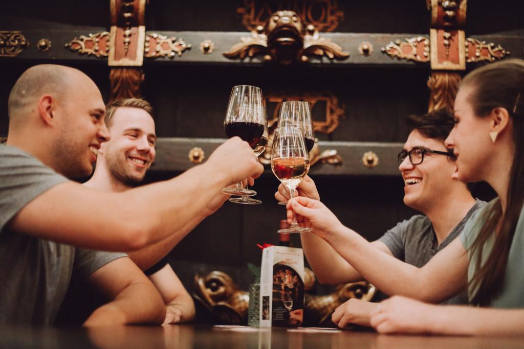 Vier Personen stoßen mit Getränken an.